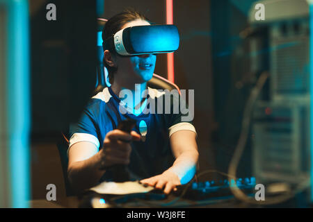 Smiling young guy in virtual reality goggles sitting at table and using joystick while having 3D experience - Stock Image