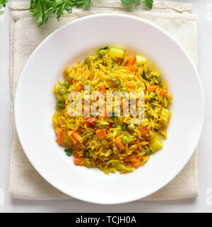 Vegetarian pilaf on plate over white stone background. Top view, flat lay - Stock Image