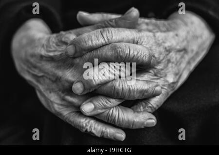 Old woman crossed fingers close up, wrinkled skin - black and white - Stock Image