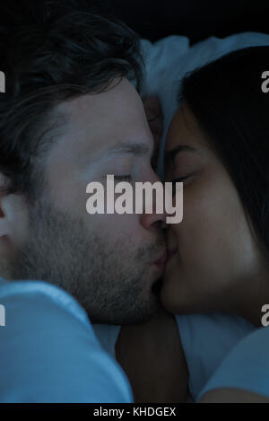 Couple kissing in bed - Stock Image