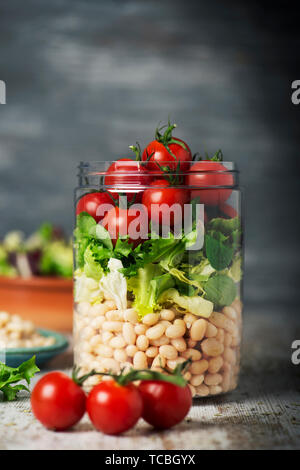 closeup of a jar salad, with cherry tomatoes, a mix of different leaf vegetables, and cooked white beans, on a rustic wooden table against a gray back - Stock Image