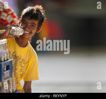 Indian boy drinking from bottle of cold drink in India. - Stock Image