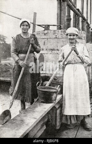 Two women doing building work, mixing cement, in a suburb of Vienna, Austria. - Stock Image