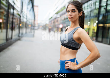Beautiful happy fit woman running and exercising outdoor - Stock Image
