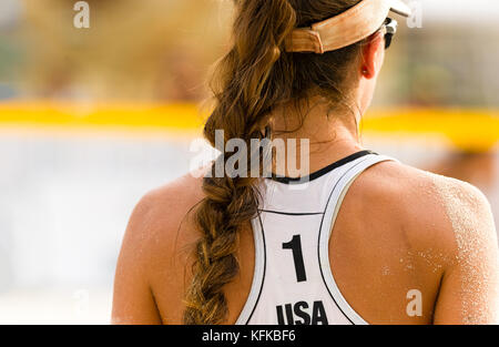 Volleyball beach serving is a female beach volleyball player getting ready to serve the ball. - Stock Image