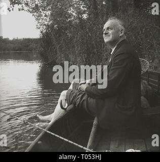 1950s, man sitting in a boat fishing with his trousers rolled up and his feet in the water, England. UK - Stock Image