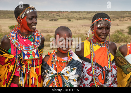 Masai women wearing colorful traditional dress, singing in a village near the Masai Mara, Kenya, Africa - Stock Image