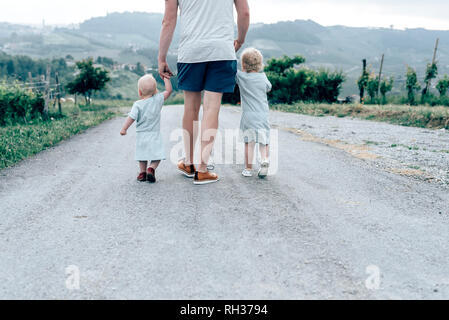 Father walking with two children - Stock Image