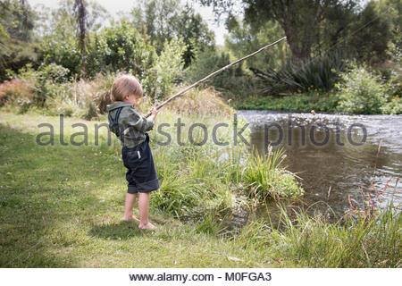 Little boy standing with old-fashioned fishing rod on a river shore - Stock Image