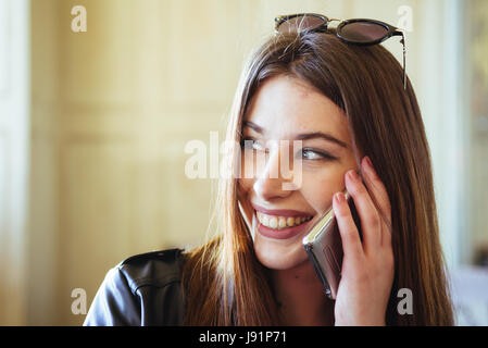 Young beautiful brunette talking   to her mobile phone while drinking a coffee and smiling - Stock Image