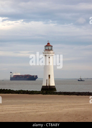 September 2011. Container ship passes the lighthouse at New Brighton, Wallasey, Merseyside - Stock Image