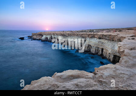 View of cliff with sea caves at sunset on Cape Greco near Ayia Napa, Cyprus (HDR image) - Stock Image