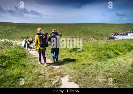Holidaymakers walking along a footpath leading down to Polly Porth Joke in Newquay in Cornwall. - Stock Image