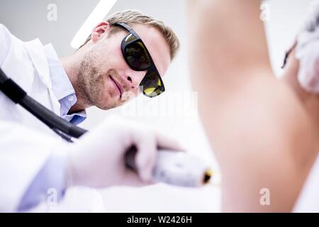 Dermatologist using laser hair removal treatment for under arms. Laser hair removal permanently destroys the root of the hair follicles by using pulse - Stock Image