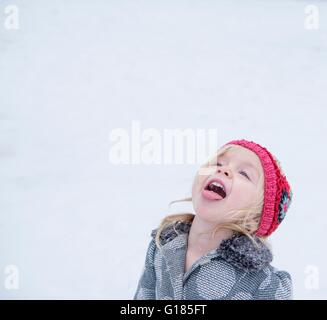 Toddler sticking out tongue to taste snow - Stock Image