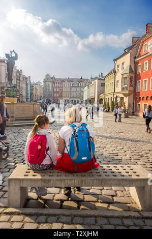 Woman and young girl sitting on a bench talking  in the old town square in the Polish city of Poznan Poland with its brightly coloured houses - Stock Image