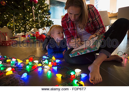 Mother and son making list Christmas string lights - Stock Image
