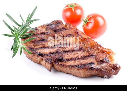 Strip steak on white plate. Rosemary and tomatoes garnish. - Stock Image