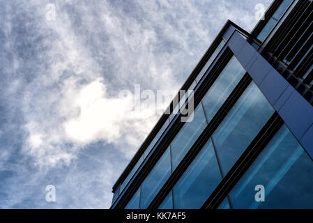 Modern business building with an abstract architecture slant of everyday modernity with a blue and white sky - Stock Image