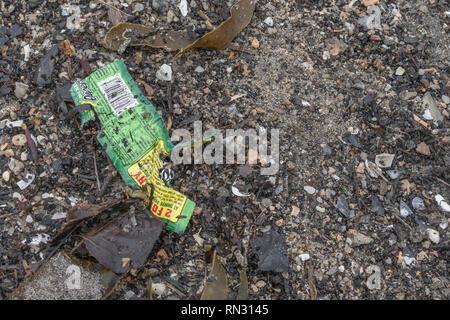 Plastic food packaging on coastal beach in Cornwall. Metaphor 'war on plastic', plastic waste, plastic rubbish in the UK. - Stock Image