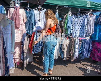 On a hot, summer day, a pretty young woman is browsing clothes at an outdoor market, in Sheringham, Norfolk, England, UK. - Stock Image