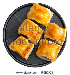 Five homemade sausage rolls on a round metal plate. Cut out on a white background. - Stock Image