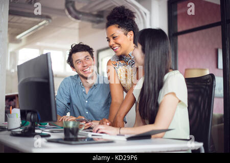 Coworkers smiling in front of computer monitor - Stock Image