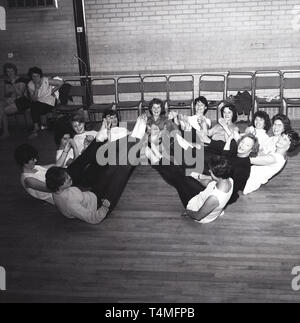 1960s, historical, a group of happy ladies in their leggings on the floor doing a yoga or keep fit class at the local sports hall. Two ladies sitting  watching the proceedings do not appear keen as they smoke a cigarette. - Stock Image
