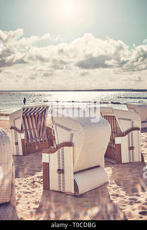 Retro stylized picture of wicker beach chairs on a beach against the sun with lens flare. - Stock Image