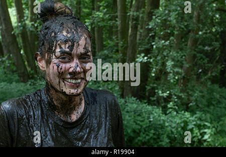 Smiling young woman covered in mud, even her teeth - Stock Image
