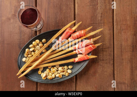 Prosciutto-wrapped Italian grissini with wine and roasted almonds, top view. Italian antipasti with parma ham, shot from the top - Stock Image