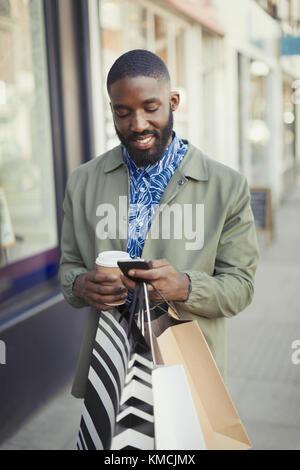 Smiling young man with coffee and shopping bags texting with cell phone on urban sidewalk - Stock Image