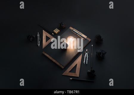 Creative idea for engineering, architecture or construction. Light bulb shining in black on black flat lay with crumpled paper balls, rulers, pencils  - Stock Image