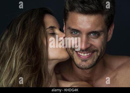 Man smiling as woman kisses his cheek - Stock Image