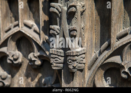 The intricate wooden carvings on one of the doors of the bombed-put ruins of Coventry Cathedral in the UK. - Stock Image