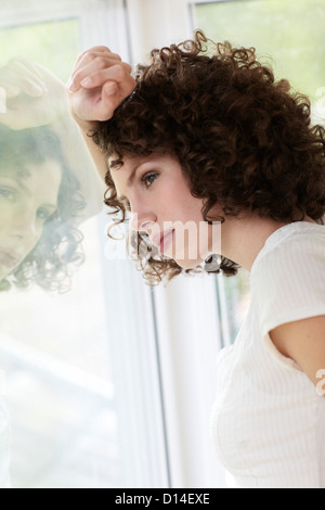 young woman standing by the window - Stock Image