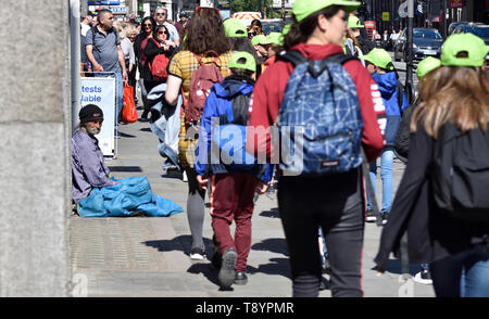 London, England, UK. Homeless man in the steet with a group of schoolchildren walking past - the Strand - Stock Image