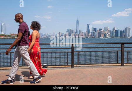 A couple walk hand in hand on Liberty Island with the New York City skyline in the background, including Lower Manhattan and the Freedom Tower - Stock Image