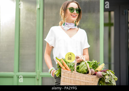 Portrait of a young woman with bag full of fresh raw vegetables standing outdoors near the green wall - Stock Image