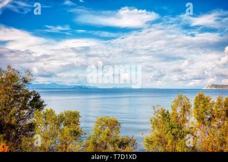 Calm sea, sky and clouds framed by trees. Seashore landscape of cukurbuk bay in Bodrum, Gumusluk, Mugla. - Stock Image