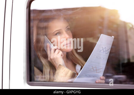 Portrait of a beautiful serious business woman advising someone on the phone about financial documents - Stock Image