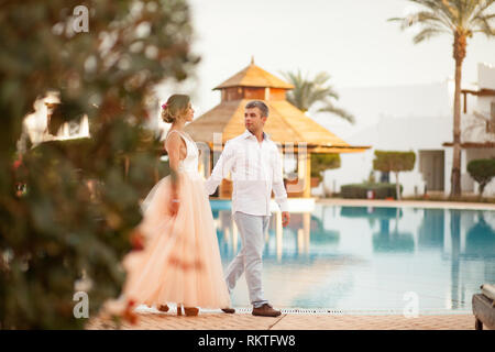 Happy newlyweds walk holding hands on the villa next to the swimmimg pool during the honeymoon in Egypt. - Stock Image