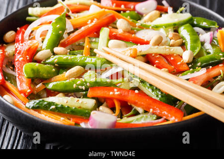 Asian salad of carrots, peas, peppers, cucumbers and onions close-up on a plate on the table. horizontal - Stock Image