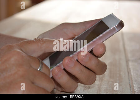 Woman using smartphone, finger on touchscreen - Stock Image