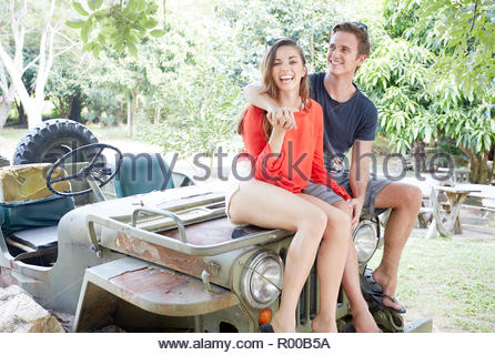 Young couple sitting on back of tractor - Stock Image