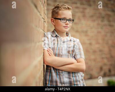 Boy, 9 years, leaning against a wall, Portrait, Germany - Stock Image