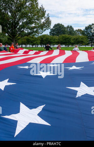 USA Maryland MD Baltimore Fort McHenry visitors hold up a large replica of the flag that was flying when Francis Scott Key wrote the Anthem poem - Stock Image