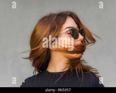 Pretty teen girl blonde hair portrait blowing wind with sunglasses looking away aside serious - Stock Image
