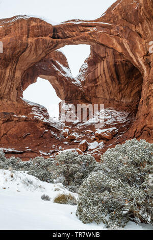 Double Arch under snow, The Windows, Arches National Park, Moab, Utah USA - Stock Image
