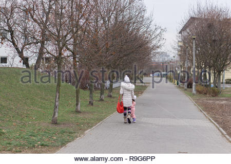 Poznan, Poland - December 2, 2018: Woman and girl in warm clothes walking on a walkway at the Stare Zegrze district on a cloudy cold day. - Stock Image